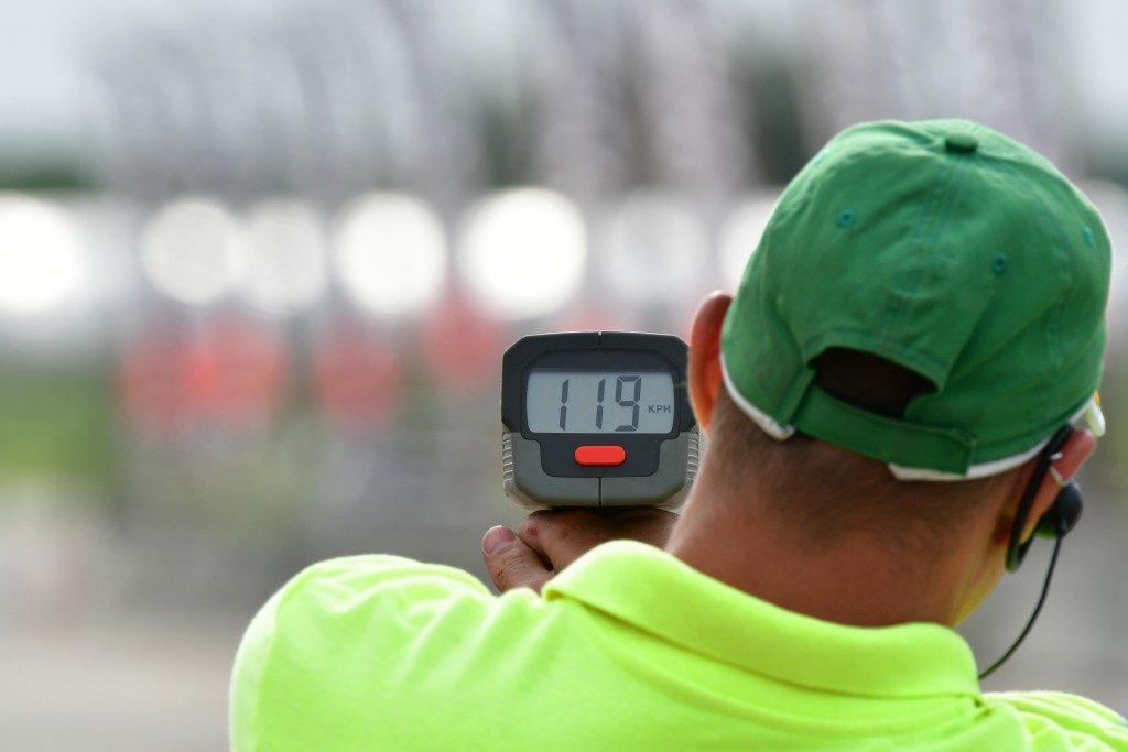 man in green shirt using a radar gun