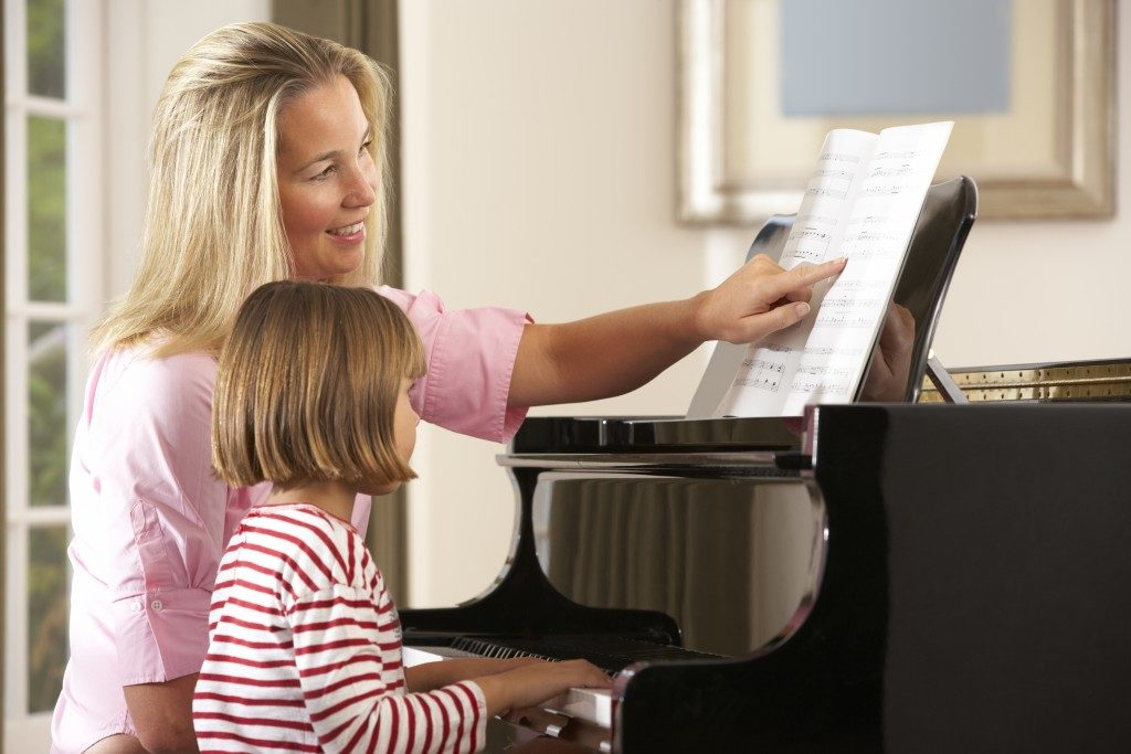girl playing piano in music lesson