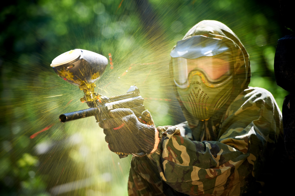 Paintball sport player wearing protective mask aiming gun and shotted down with paint splash in summer